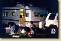 Family around the campfire near their rv trailer rental